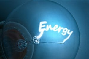"Close up on illuminated blue light bulb filament which spells the word ""Energy""."